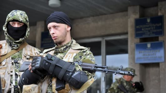 Armed men in military fatigues stand guard outside a regional administration building they seized in the eastern Ukrainian city of Slavyansk.